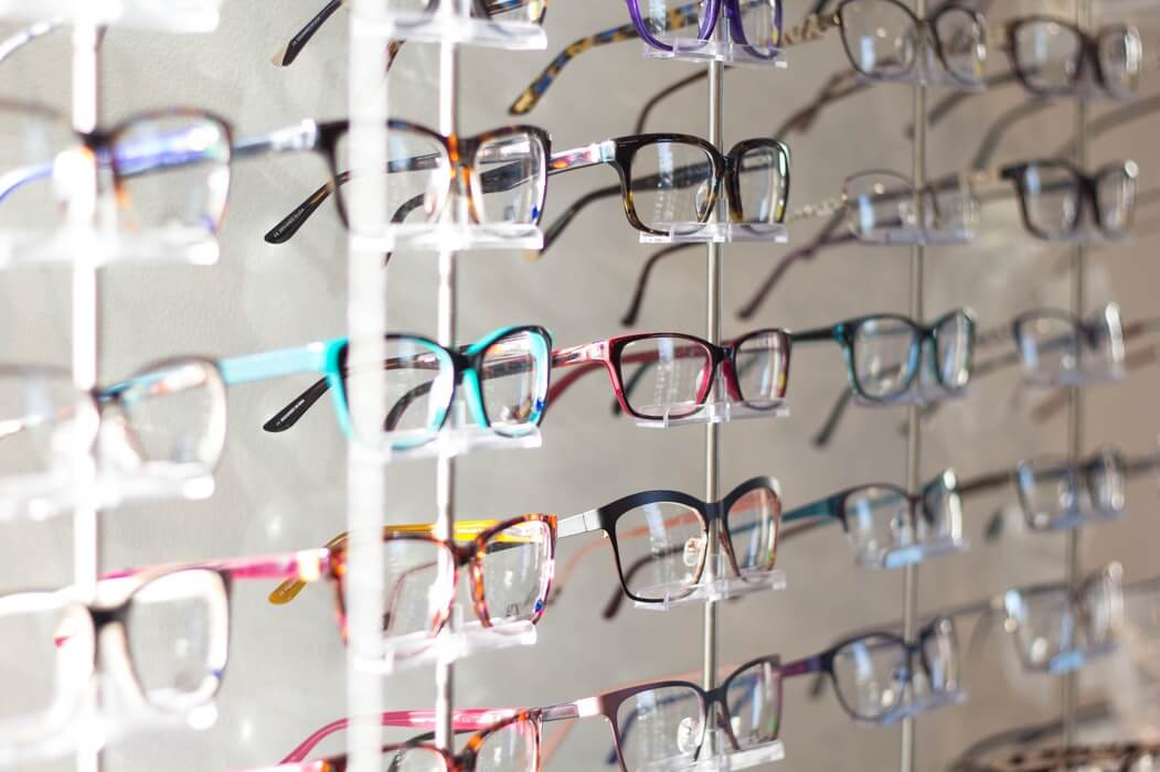 Rows of glasses frames arranged in an opticians.